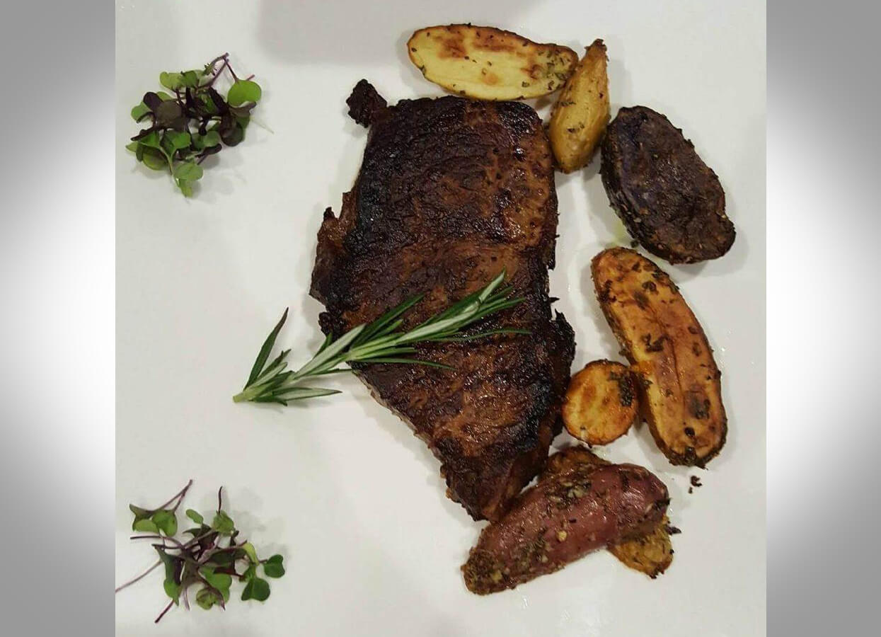 Showing a fine cut of steak served with roasted potatoes.