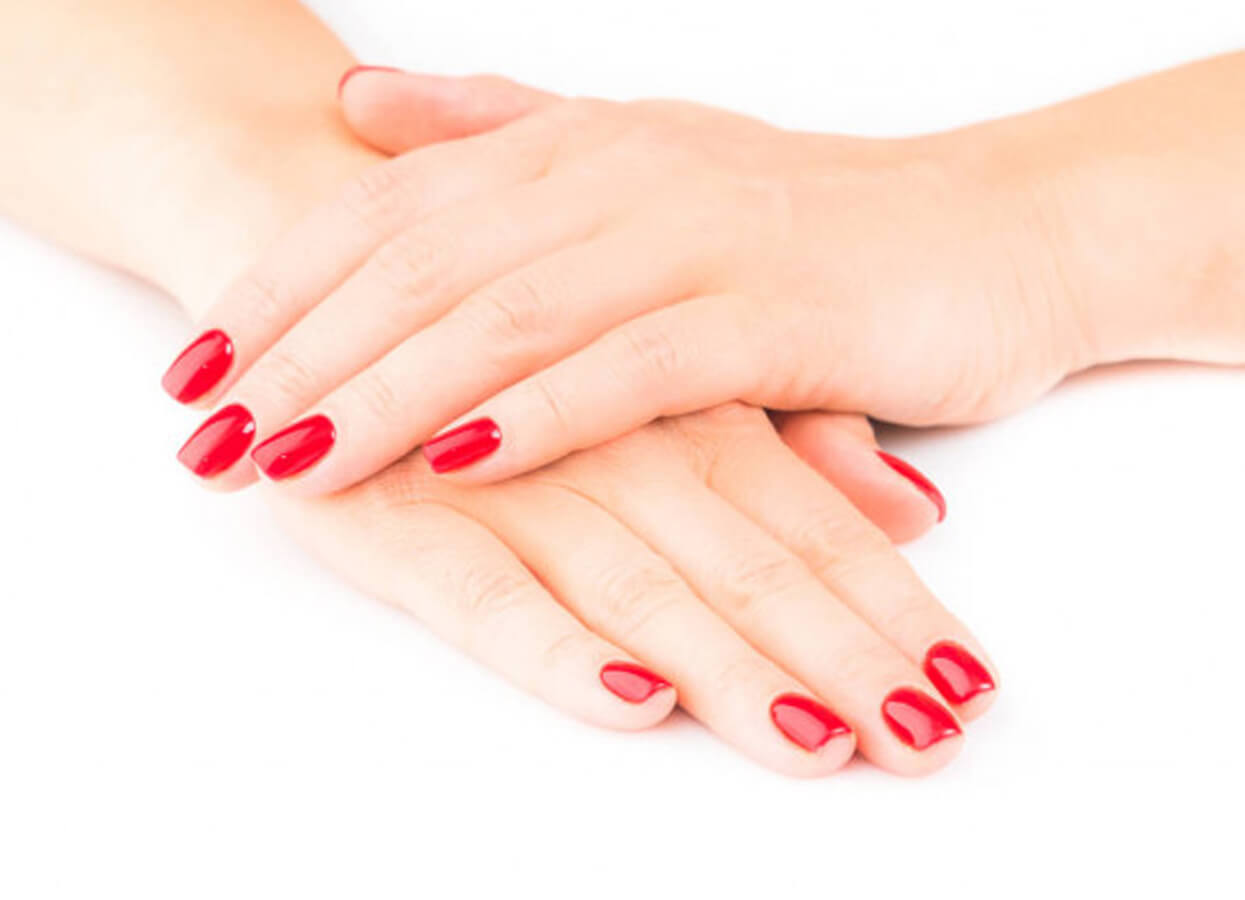 Showing a woman with red painted nails.